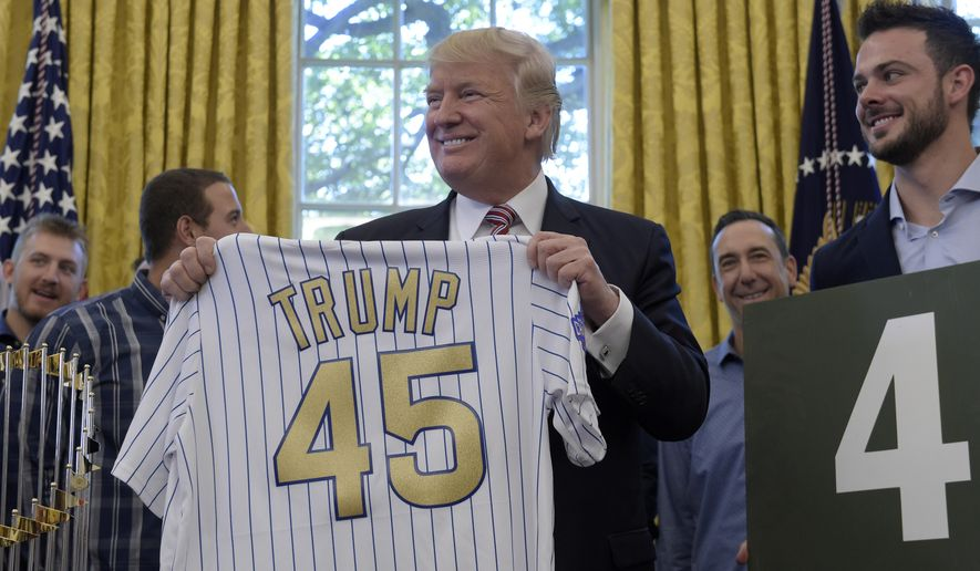 President Donald Trump holds up a Chicago Cubs jersey as he meets with members of the 2016 World Series Champions Chicago Cubs, Wednesday, June 28, 2017, in the Oval Office of the White House in Washington. Cubs third baseman Kris Bryant is at right. (AP Photo/Susan Walsh)