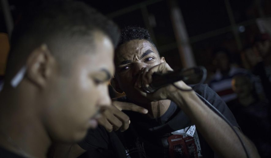 In this June 8, 2017 photo, rap artists engage in a rap battle in the City of God slum of Rio de Janeiro, Brazil. For the young men, freestyle rap battles are a way to express frustration with the violence that permeates their daily lives. (AP Photo/Leo Correa)