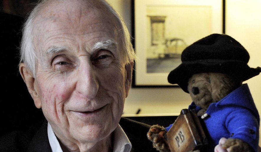 In this June 12, 2015, file photo, Michael Bond poses with a soft toy version of Paddington bear. Publisher HarperCollins says Bond, creator of globe-trotting teddy Paddington bear, died on Tuesday June 27, 2017, aged 91. (Nick Ansell/PA via AP)