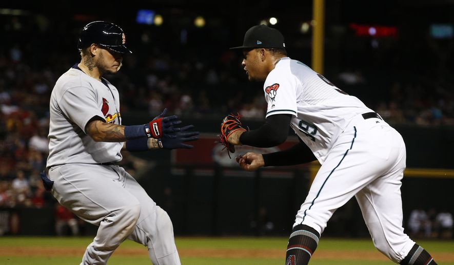 Arizona Diamondbacks' Taijuan Walker, right, reaches over to tag out St. Louis Cardinals' Yadier Molina after an infield grounder during the sixth inning of a baseball game, Tuesday, June 27, 2017, in Phoenix. (AP Photo/Ross D. Franklin)