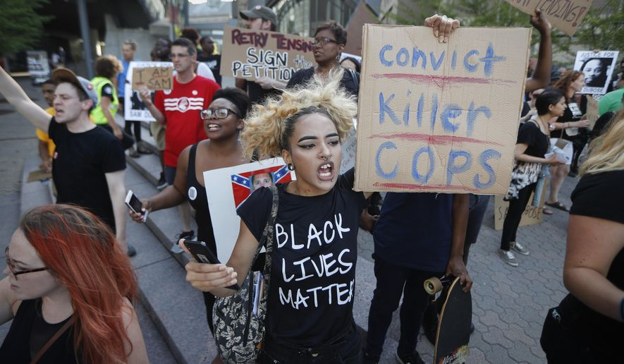 Protesters chant outside Nippert Stadium before a soccer game during a demonstration on the University of Cincinnati campus demanding that a white former police officer, Ray Tensing, be tried a third time in the fatal shooting of an unarmed black motorist, Wednesday, June 28, 2017, in Cincinnati. A mistrial was declared twice in the murder and voluntary manslaughter case of Tensing, who was a University of Cincinnati police officer when he shot Sam DuBose during a 2015 traffic stop. (AP Photo/John Minchillo)