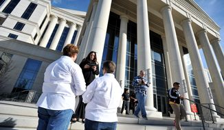 A same sex couple take their wedding vows in front of the Duval County Courthouse Tuesday morning, Jan. 6, 2015, in Jacksonville, Fla. U.S. District Judge Robert L. Hinkle's ruling that Florida's same-sex marriage ban is unconstitutional took effect early Tuesday in all 67 counties in the state. (AP Photo/The Florida Times-Union, Bob Self)