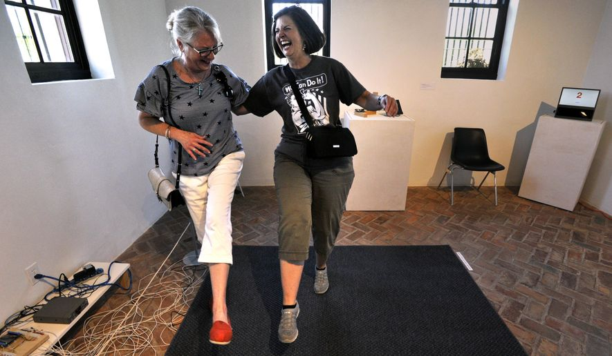 """In this Friday, June 16, 2017, Debbie Albrand, of McKinney, left, and Sue Harrington of Wichita Falls, playfully can-can on an interactive musical rug in one of the Old Jail Art Center's jail cells, in Albany, Texas.  The Cell Series features Joel Sampson's """"Sound Advice - Beats and Other Bits"""", a collection of devices which generate sound. The exhibit will be on display until August 26. (Ronald W. Erdrich/The Abilene Reporter-News via AP)"""