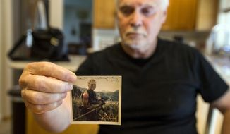 ADVANCE FOR USE SATURDAY, JULY 1 - In this June 22, 2017 photo, Robert Martin holds a picture of himself at his home in Coeur d'Alene, Idaho, holding 2-month-old Roberta Sunday after finding her in a bunker in Vietnam. Martin's lone contact with Roberta Sunday was that one day in August 1970. While he's thought about her a lot over the past 47 years, he recently decided he'd like to re-connect with her. He said finding Sunday would bring something positive to his war experience. (Loren Benoit/Coeur D'Alene Press via AP)
