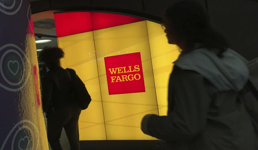 FILE - In this Thursday, Oct. 13, 2016, file photo, commuters walk by a Wells Fargo ATM location at New York's Penn Station. On Wednesday, June 28, 2017, the Federal Reserve gave the green light to all 34 of the biggest banks in the U.S. to raise their dividends and buy back shares, judging their financial foundations sturdy enough to withstand a major economic downturn. Those allowed to raise dividends or repurchase shares include the four biggest U.S. banks: JPMorgan Chase, Bank of America, Citigroup and Wells Fargo. (AP Photo/Swayne B. Hall, File)