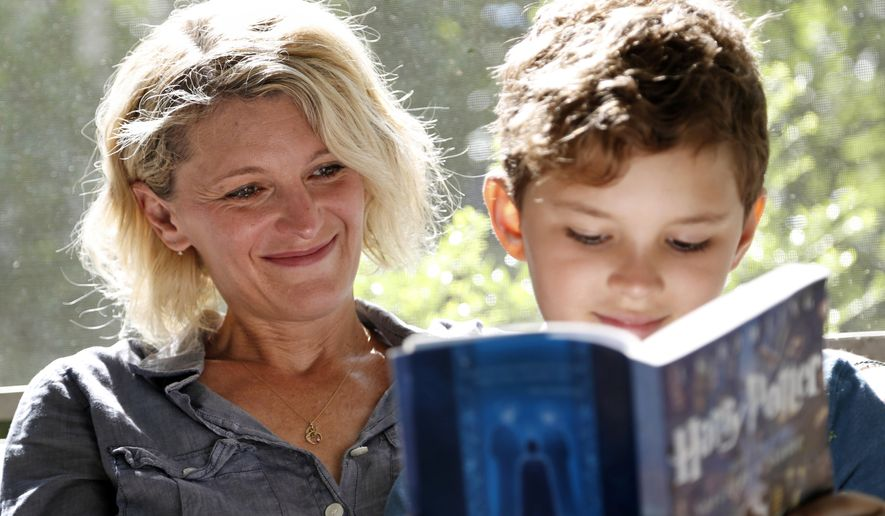 "Theo Galkin, 8, rereads a favorite part of ""Harry Potter and the Sorcerer's Stone"" while posing for a picture with his mother Chloe Galkin at their home in South Orange, N.J., Wednesday, June 28, 2017. As the 20th anniversary of the initial publishing of the first Harry Potter book is celebrated this week, another generation is being introduced to Harry, Hogwarts and all the rest of the magical world created by author J.K. Rowling. (AP Photo/Seth Wenig)"