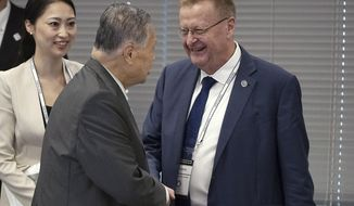International Olympic Committee (IOC) Vice President John Coates, right, and Tokyo 2020 Olympics President Yoshiro Mori, center, shake hands prior to the IOC Coordination Commission opening plenary for the Olympic Games Tokyo 2020 in Tokyo Wednesday, June 28, 2017. (AP Photo/Eugene Hoshiko)
