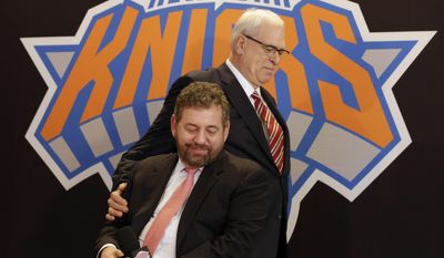 In this March 18, 2014, file photo, New York Knicks new team president Phil Jackson puts his hand on team owner James Dolan, seated, during a news conference where Jackson was introduced, at New York's Madison Square Garden. (AP Photo/Richard Drew, File) **FILE**