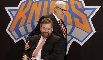 FILE - In this March 18, 2014, file photo, New York Knicks new team president Phil Jackson puts his hand on team owner James Dolan, seated, during a news conference where Jackson was introduced, at New York's Madison Square Garden. The Knicks and Jackson parted ways Wednesday morning, June 28, 2017, ending a three-year tenure that saw plenty of tumult and not a single playoff appearance.(AP Photo/Richard Drew, File)