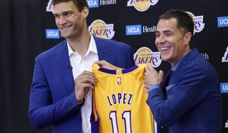 Brook Lopez, left, a new member of the Los Angeles Lakers, holds up his jersey with Lakers general manager Rob Pelinka during a news conference at Toyota Sports Center in El Segundo, Calif., on Wednesday, June 28, 2017. (AP Photo/Chris Pizzello)