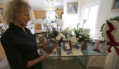 In this Tuesday, June 20, 2017 photo, Violet Martin in her Grand Junction, Colo. home, holds a photo of a full moon from the night her late husband Bob died. The two reconnected after decades apart, and married recently on June 5 after they found out his cancer was terminal. Violet's just grateful they had time together in the end, as Bob died five days after they married, and she loves telling their love story.  (Christopher Tomlinson/The Grand Junction Daily Sentinel via AP)