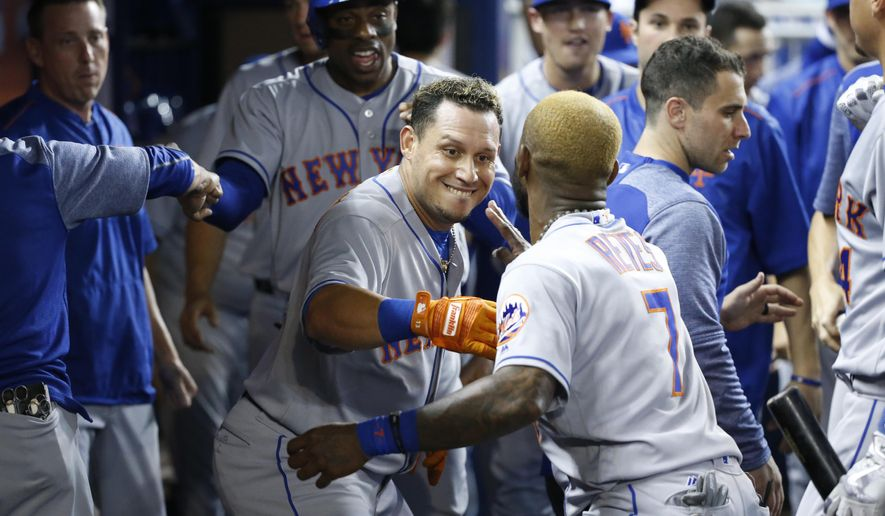 New York Mets' Asdrubal Cabrera, center, and Jose Reyes (7) celebrate after Cabrera hit a home run scoring Curtis Granderson during the first inning of the team's baseball game against the Miami Marlins, Wednesday, June 28, 2017, in Miami. (AP Photo/Wilfredo Lee)