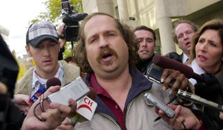 FILE - In this Thursday, Oct. 23, 2003, file photo, Kirk Jones of Canton, Mich., the man who survived a plunge over Niagara Falls, talks to reporters after being released from custody in St. Catherines, Ontario. Jones, who died after plunging over Niagara Falls in an apparent stunt with an inflatable ball might have brought a boa constrictor along for the ride, the Niagara Gazette reported Wednesday, June 28, 2017, that police found a website with a photo of Jones and the snake previewing Jones' plans. An unoccupied large plastic ball he apparently planned to ride over the falls was found empty below the falls in April. (AP Photo/David Duprey, File)