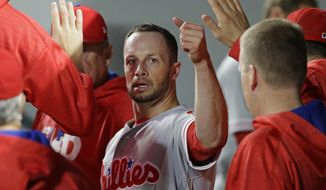 Philadelphia Phillies' Daniel Nava is greeted in the dugout after he scored in the eighth inning of the team's baseball game against the Seattle Mariners, Tuesday, June 27, 2017, in Seattle. (AP Photo/Ted S. Warren)