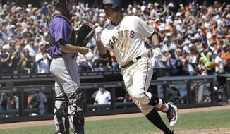 San Francisco Giants' Jae-Gyun Hwang, of South Korea, crosses the plate next to Colorado Rockies catcher Tom Murphy after hitting a solo home run during the sixth inning of a baseball game in San Francisco, Wednesday, June 28, 2017. (AP Photo/Jeff Chiu)