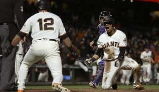 San Francisco Giants' Gorkys Hernandez, right, celebrates with Joe Panik (12) after scoring the game winning run against the Colorado Rockies in the 14th inning of a baseball game Tuesday, June 27, 2017, in San Francisco. Hernandez scored on a single by Giants' Denard Span. (AP Photo/Ben Margot)