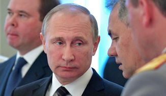 Russian President Vladimir Putin, center, listen to Defence Minister Sergei Shoigu at a meeting with graduates of military and police academies in the Kremlin in Moscow, Russia, Wednesday, June 28, 2017. Putin has pledged to continue efforts to beef up the Russian military and law-enforcement agencies. At left, Chief of presidential administration Anton Vayno. (Alexei Druzhinin/Sputnik, Kremlin Pool Photo via AP)