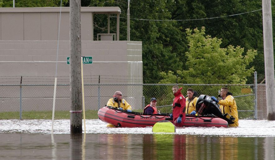 In this photo taken June 25, 2017, firefighters float a driver they just rescued from a car stuck in the flooded intersection of West Michigan and South Center in Michigan's Saginaw Township. (Jeff Schrier/The Saginaw News via AP)