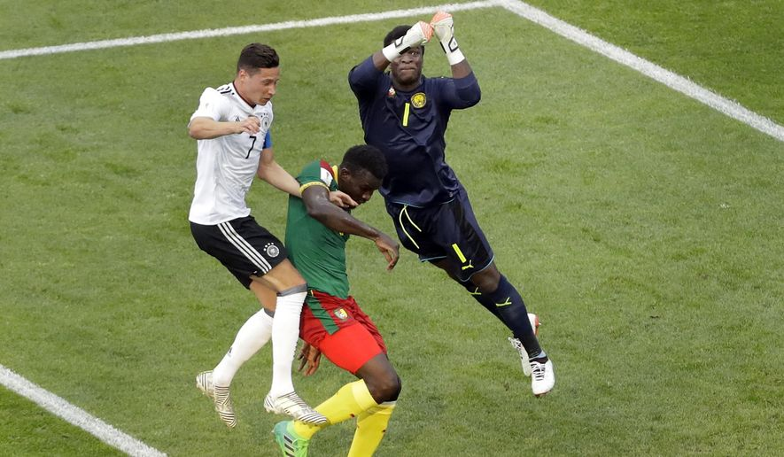 Cameroon goalkeeper Fabrice Ondoa, right, and Germany's Julian Draxler, left, challenge for the ball during the Confederations Cup, Group B soccer match between Germany and Cameroon, at the Fisht Stadium in Sochi, Russia, Sunday June 25, 2017. (AP Photo/Sergei Grits)