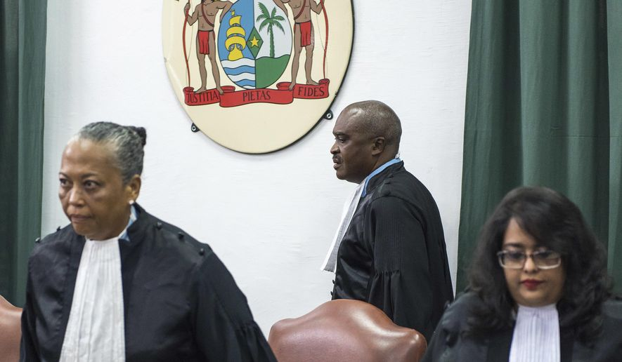 Prosecutor Roy Elgin, center, and judges Cynthia Valstein-Montnor, left, and Rewita Chatterpal, take their seats at a court in Paramaribo, Suriname, Wednesday, June 28, 2017. Elgin is calling for a 20-year prison sentence for Suriname President Desi Bouterse for his role in the December 1982 killing of 15 prominent political opponents in the South American country. (AP Photo/Pieter Van Maele)
