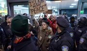 FILE - In this Jan. 28, 2017, file photo, protesters are surrounded by police officers and travelers as they pass through an exit of Terminal 4 at John F. Kennedy International Airport in New York, after earlier in the day two Iraqi refugees were detained while trying to enter the country. U.S. Customs and Border Protection officers will be key players in putting President Donald Trump's revised travel ban into effect on Thursday, June 29, affecting visitors from six mostly Muslim countries. (AP Photo/Craig Ruttle, File)