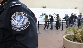 Pedestrians crossing from Mexico into the United States at the Otay Mesa Port of Entry wait in line in San Diego on Dec. 10, 2015. (Associated Press) **FILE**