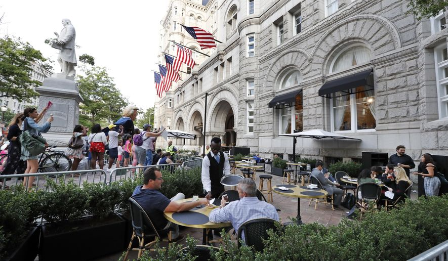 Protesters yell at patrons at the outdoor seating area at the Trump International Hotel, Wednesday, June 28, 2017, in Washington. President Donald Trump is attending a fundraiser at the hotel. (AP Photo/Alex Brandon)