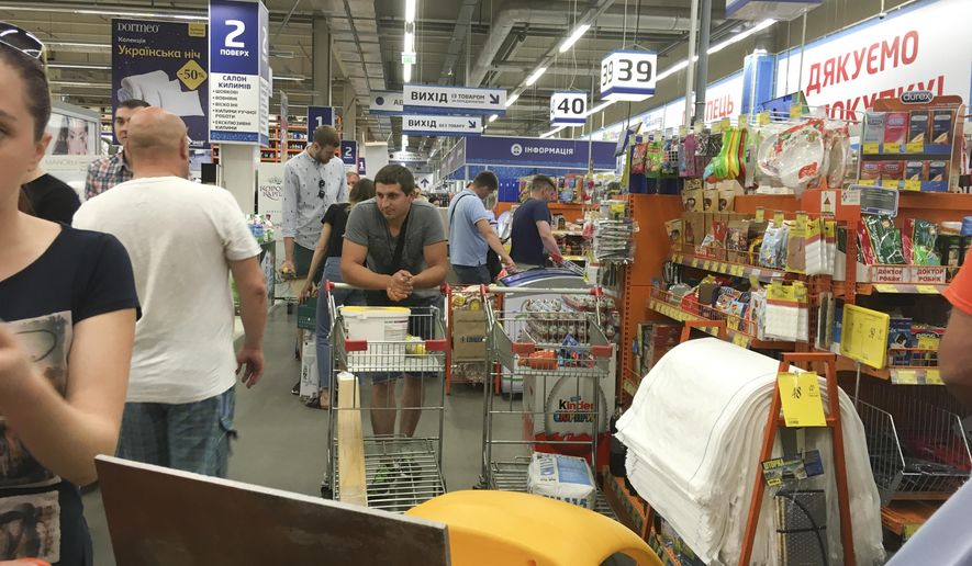 People queue for their turn to pay at a slowly working cash desk in a building supermarket in Kiev, Ukraine, Wednesday, June 28, 2017.  The cyberattack ransomware that has paralyzed computers across the world hit Ukraine hardest Tuesday, with victims including top-level government offices, energy companies, banks, cash machines, gas stations, and supermarkets.  (AP Photo/Efrem Lukatsky)