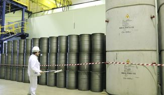 In this March 23, 2016, file photo, a worker checks the radiation level on barrels in a storage of nuclear waste taken from the 4th unit destroyed by the 1986 explosion at the Chernobyl nuclear power plant, Chernobyl, Ukraine.  A new and highly virulent outbreak of data-scrambling software — apparently sown in Ukraine — caused disruption across the world Tuesday, June 27, 2017.  The virus hit the radiation-monitoring at Ukraine's shuttered Chernobyl power plant, site of the world's worst nuclear accident, forcing it into manual operation. (AP Photo/Efrem Lukatsky)