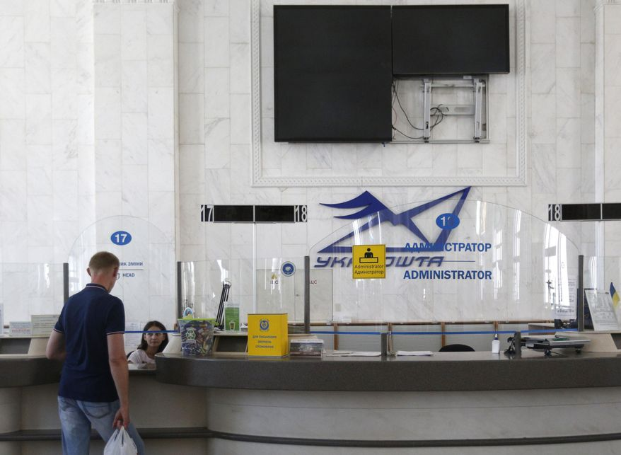 A man talking to an employee of Ukrposhta (Ukrainian post) in Kiev, Ukraine, Wednesday, June 28, 2017. The cyberattack ransomware that has paralysed computers across the world hit Ukraine hardest Tuesday, with victims including top-level government offices, energy companies, banks, cash machines, gas stations, and supermarkets. (AP Photo/Sergei Chuzavkov)