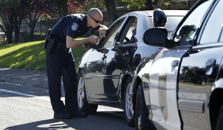 FILE - In this Nov. 12, 2012 file photo, a Sacramento Police Officer makes a traffic stop in Sacramento, Calif. California Gov. Jerry Brown signed a bill Tuesday, June 27, 2017, to end the practice of Californians losing their driver's license because of unpaid traffic fines. The law takes effect July 1. (AP Photo/Rich Pedroncelli, File)