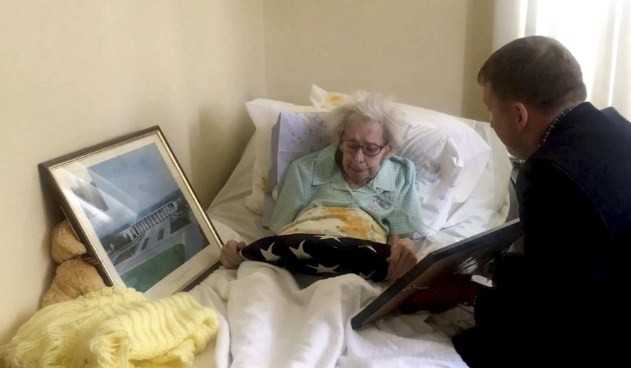 In this image taken from video provided by Stringr, Captain Zacharia Fike of Purple Hearts Reunited presents a flag and Purple Heart to Mildred Stotzer at the Sunrise of Westfield assisted living facility in Westfield, N.J., Wednesday, June 28, 2017. The flag and medals belonged to Stotzer's brother, Master Sgt. Frederick Boelzle, was killed in Belgium in December 1944. (Stringr via AP)