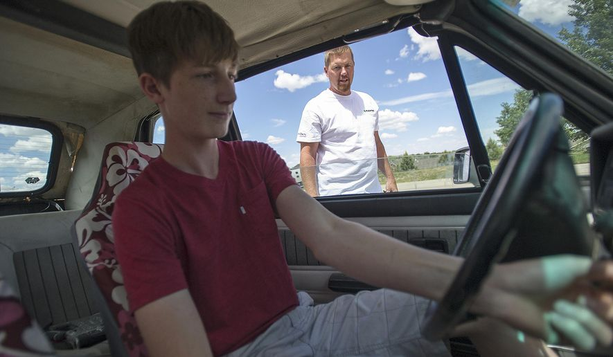 ADVANCE FOR WEDNESDAY JUNE 28 AND THEREAFTER - In a June 13, 2017 photo, Tyler Sikkenga fires up the noisy engine Tuesday of his 1987 Volkswagen Karmann Ghia Cabriolet outside of his home in Gillette, Wyo., as his father, Nate, watches. The duo turned the once conservative commuter into a roaring frankencar by replacing the rear axle with a single wheel.  (Ed Glazar/Gillette News Record via AP)