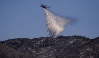A helicopter drops water on a ridge line during a wildfire near Huer Huero Road in Santa Margarita, Calif., Tuesday, June 27, 2017. (Joe Johnston/The Tribune (of San Luis Obispo) via AP)