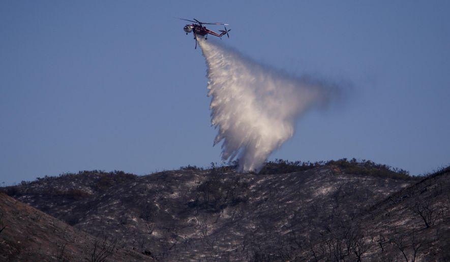 A helicopter drops water on a ridge line during a wildfire near Huer Huero Road in Santa Margarita, Calif., Tuesday, June 27, 2017. (Joe Johnston/The Tribune (of San Luis Obispo) via AP)