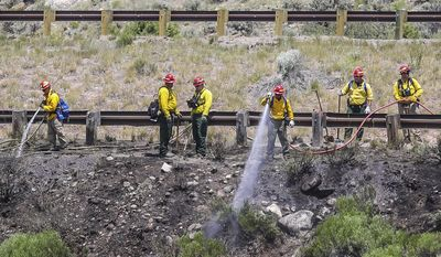 Fire crews work to put out a brush fire on the eastbound side of Interstate 70 on Wednesday, June 28, 2017, in Avon, Colo. The Vail Valley is under a Red Flag Warning due to hot temperatures and gusty winds. (Chris Dillmann/Vail Daily via AP)