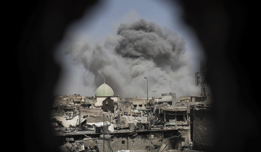 A bomb exploded behind the al-Nuri mosque complex, as seen through a hole in the wall of a house, as Iraqi special forces moved toward Islamic State militant positions in the Old City of Mosul on Thursday. (Associated Press)