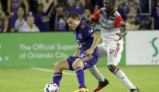 D.C. United's Patrick Nyarko, right, grabs Orlando City's Donny Toia by the arm as they try to get possession of the ball during the second half of an MLS soccer game, Wednesday, May 31, 2017, in Orlando, Fla. Orlando Won 2-0. (AP Photo/John Raoux)