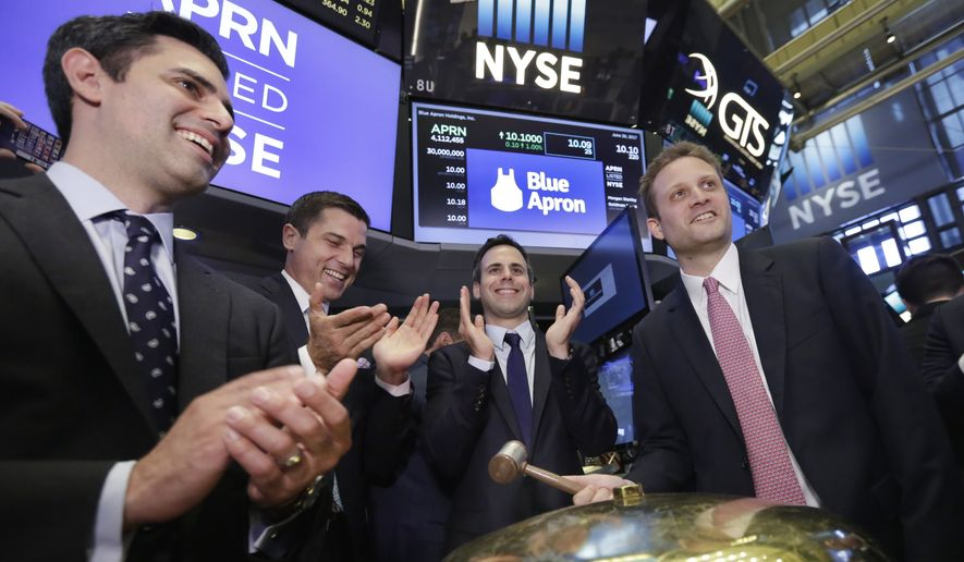 Blue Apron CEO Matt Salzberg, right, with fellow company co-founders Ilia Papas, left, and Matt Wadiak, second from right, rings a ceremonial bell on the New York Stock Exchange floor as their IPO begins trading, Thursday, June 29, 2017. NYSE President Tom Farley is second from left. (AP Photo/Richard Drew) ** FILE **