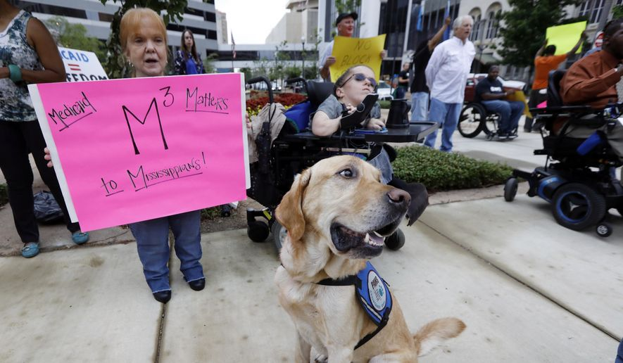 """Jones,"" an assistance dog, watches the goings on, as her owner, Cindy Singletary, right, and her mother Bobbie Singletary, both of Biloxi, join others calling for support of Medicaid, during a peaceful protest in Jackson, Miss., Thursday, June 29, 2017. Medicaid recipients, social service activists and representatives and Medicaid supporters staged protests outside the offices of both of Mississippi's Republican senators, Thad Cochran and Roger Wicker. Cindy receives Medicaid care because of complications of dwarfism. (AP Photo/Rogelio V. Solis) ** FILE **"