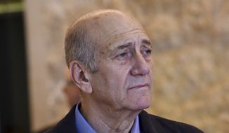 In this Dec. 29, 2015, file photo, former Israeli Prime Minister Ehud Olmert leaves the courtroom of the Supreme Court after the court ruled on his appeal in the Holyland corruption case in Jerusalem. The parole board of Israel's Prison Service on Thursday granted former Prime Minister Ehud Olmert early release from his 27-month corruption sentence. Barring any unforeseen developments, Olmert will walk free on Sunday, July 2, 2017. (Debbie Hill/Pool File Photo via AP)