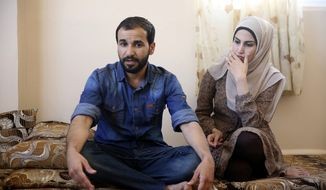 Mohammad al-Haj Ali, 28, and his wife Samah Hamidi, 25, pose for a photo during an interview in their home in Irbid, Jordan on Thursday, June 29, 2017. The family fled the Syrian war in 2012 for Jordan and was in the resettlement pipeline to the U.S. when President Donald Trump's executive order stalled the process. Once sure of his future in the U.S., al-Haj Ali had quit his job, sold the furniture and rented an apartment in the city of Rockford near his uncle's home in Illinois. The family still has five suitcases packed but has scant hope for resettlement in America. (AP Photo/Reem Saad)