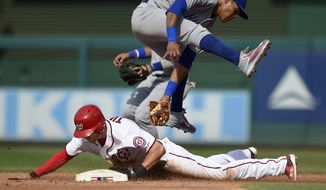 Washington Nationals' Trea Turner, front bottom, steals second against Chicago Cubs shortstop Addison Russell, top, during the third inning of a baseball game, Thursday, June 29, 2017, in Washington. (AP Photo/Nick Wass