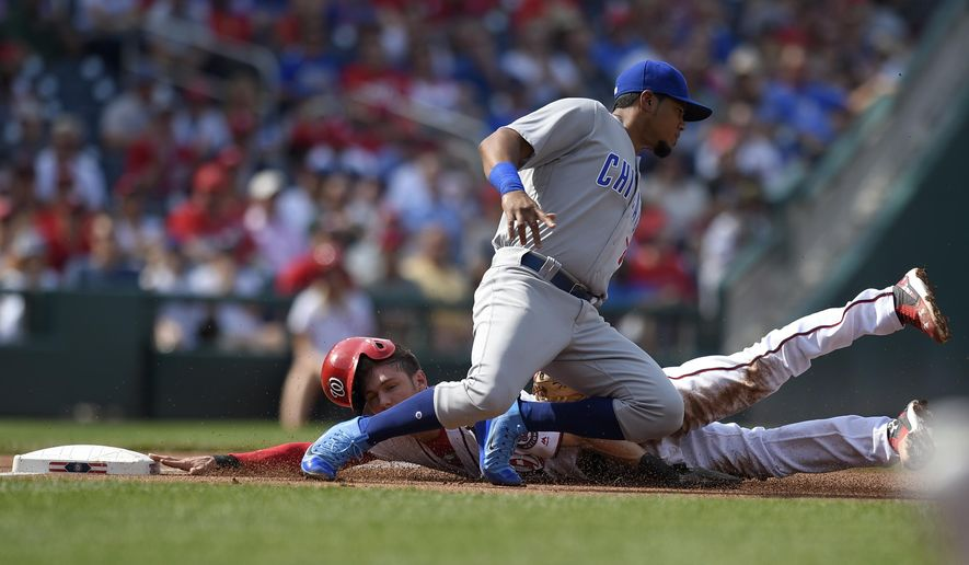 Washington Nationals' Trea Turner, back, is tagged out by Chicago Cubs third baseman Jeimer Candelario, front, as he tried to steal third during the first inning of a baseball game, Thursday, June 29, 2017, in Washington. (AP Photo/Nick Wass)