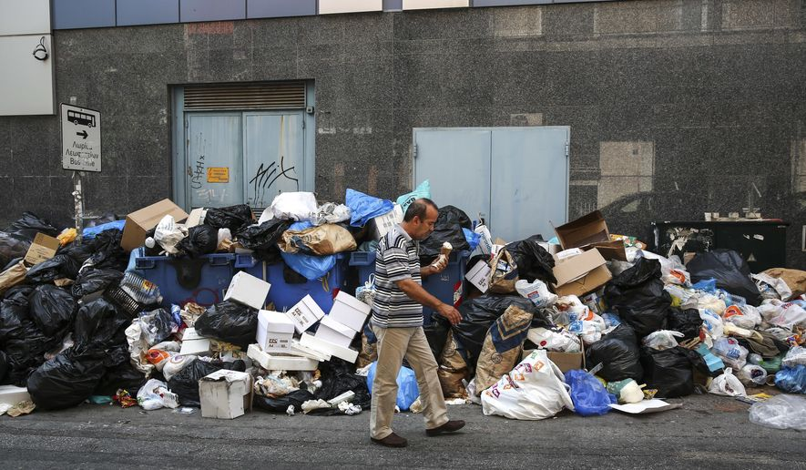 A man holds an ice cream as he makes his way past a pile of garbage in Athens, on Thursday, June 29, 2017. A strike by garbage collectors, which has lasted nearly two weeks, has left towering mounds of garbage on city streets at a time when the summer's first heatwave sent temperatures soaring. (AP Photo/Yorgos Karahalis)