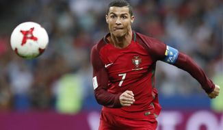 Portugal's Cristiano Ronaldo keeps his eyes on the ball during the Confederations Cup, semifinal soccer match between Portugal and Chile, at the Kazan Arena, Russia, Wednesday, June 28, 2017. (AP Photo/Pavel Golovkin)