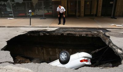 A St. Louis police officer looks over a large hole in 6th Street, Thursday, June 29, 2017, in St. Louis, that swallowed a Toyota Camry between Olive and Locust Streets. It isn't immediately clear what caused the collapse.(Christian Gooden/St. Louis Post-Dispatch via AP)