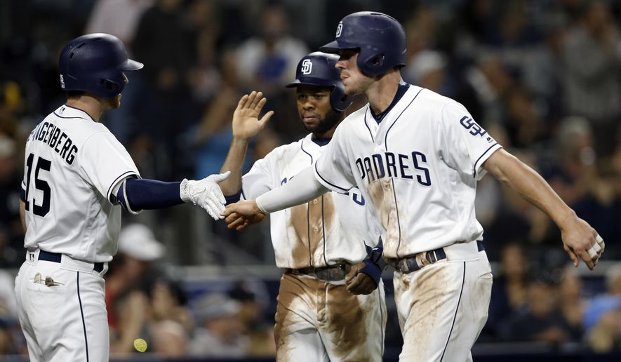 San Diego Padres' Cory Spangenberg, left, congratulates Wil Myers, right, and Manuel Margot, who scored on a triple by Hunter Renfroe during the fourth inning of the team's baseball game against the Atlanta Braves in San Diego, Wednesday, June 28, 2017. (AP Photo/Alex Gallardo)
