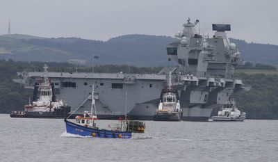 HMS Queen Elizabeth, one of two new aircraft carriers for the Royal Navy, is assisted by tugs on the Firth of Forth after leaving the Rosyth dockyard, Scotland, near Edinburgh to begin her sea worthiness trials, Monday June 26, 2017. Naval staff and contractors lined the deck of HMS Queen Elizabeth as the 280-metre, 65,000-tonne aircraft carrier moved in a three-hour operation. (Andrew Milligan/PA via AP)