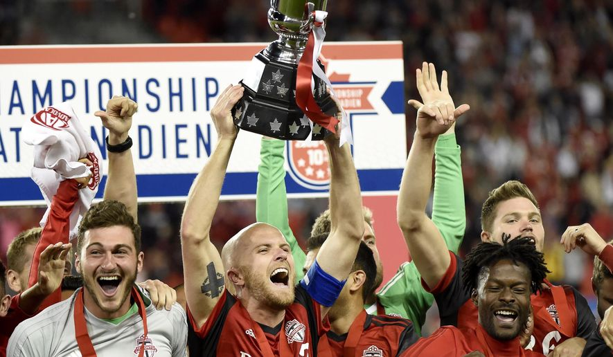 Toronto FC midfielder Michael Bradley (4) holds up the trophy as the team celebrates a win over the Montreal Impact in the Canadian championship soccer final, Tuesday, June 27, 2017, in Toronto. (Nathan Denette/The Canadian Press via AP)